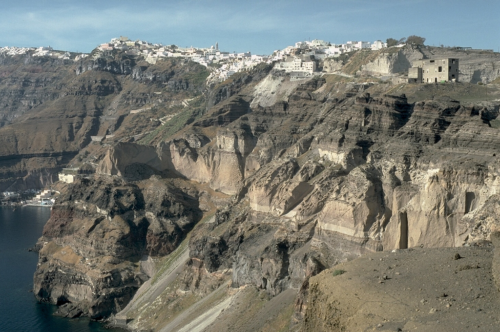 The steep eastern caldera walls of Santorini are draped by the town of Firá, many of which were built within deposits of the Minoan eruption that took place about 3,500 years ago. The most prominent unit in the caldera wall at this location is the Middle Tuff Sequence, the lighter-colored, cliff-forming unit halfway up the wall that is composed of a basal pumice deposit overlain by breccia and pyroclastic flow deposits. The Middle Tuff and the darker bedded layers overlying it were deposited during late-Pleistocene eruptions. Photo by Lee Siebert, 1994 (Smithsonian Institution).