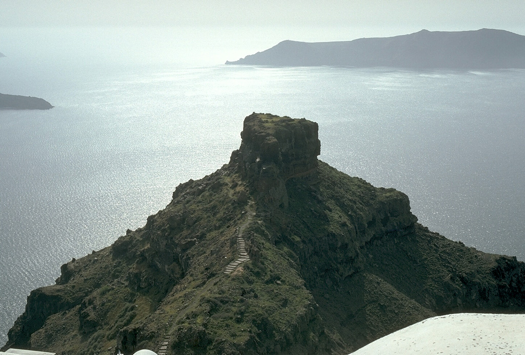 The steep inner walls of Santorini drop steeply into the caldera bay. Pyroclastic flow deposits from four caldera-forming eruptions dating back to 100,000 years ago are exposed in the caldera walls in this N-looking view. The youngest caldera was formed about 3,500 years ago during the Minoan eruption of Santorini. The flat-topped peak on the left skyline is Skaros, a remnant of a shield volcano constructed within a previous caldera. Photo by Lee Siebert, 1994 (Smithsonian Institution).