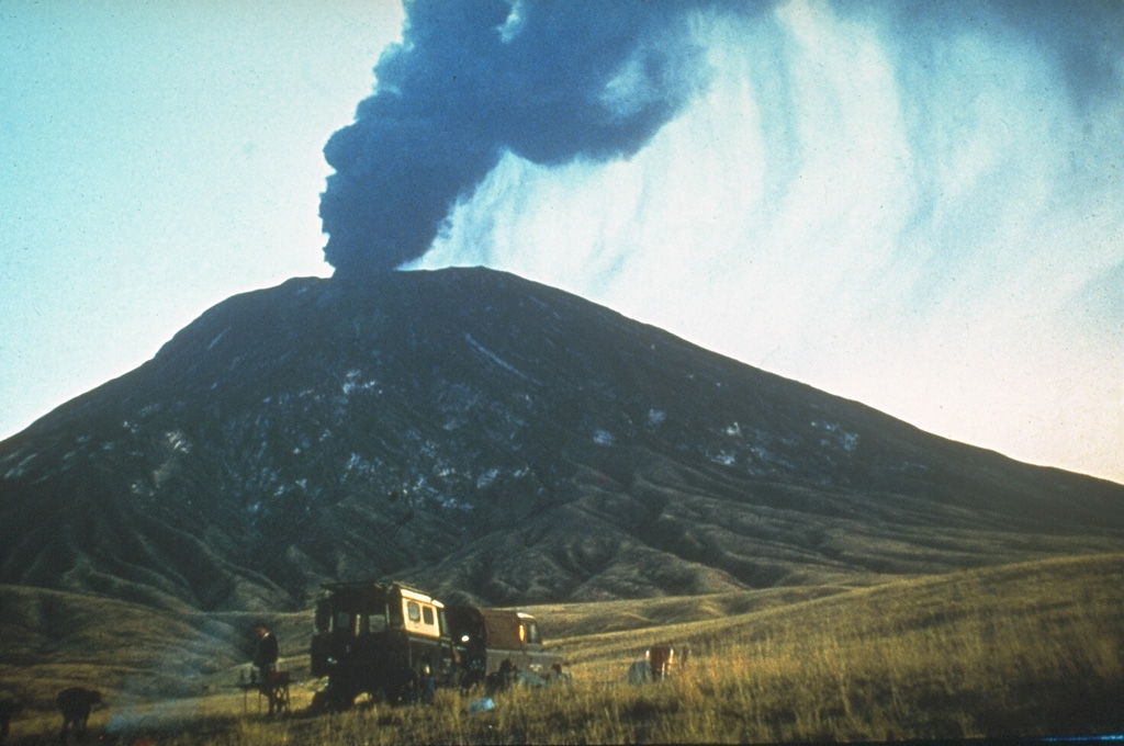 An ash plume rises above the summit of Ol Doinyo Lengai in 1966, near the end of an eruption that began in 1960. Quiet extrusion of carbonatite lava apparently took place from 1960 to 1966, although few direct observations were made. In early August 1966 activity changed to vigorous ash eruptions. A powerful explosive eruption was observed on 22 August. Explosive activity was also reported on 28 October and the volcano was reported to be quiescent in late December 1966. Photo by Gordon Davies, 1966 (courtesy of Celia Nyamweru, Kenyatta University).