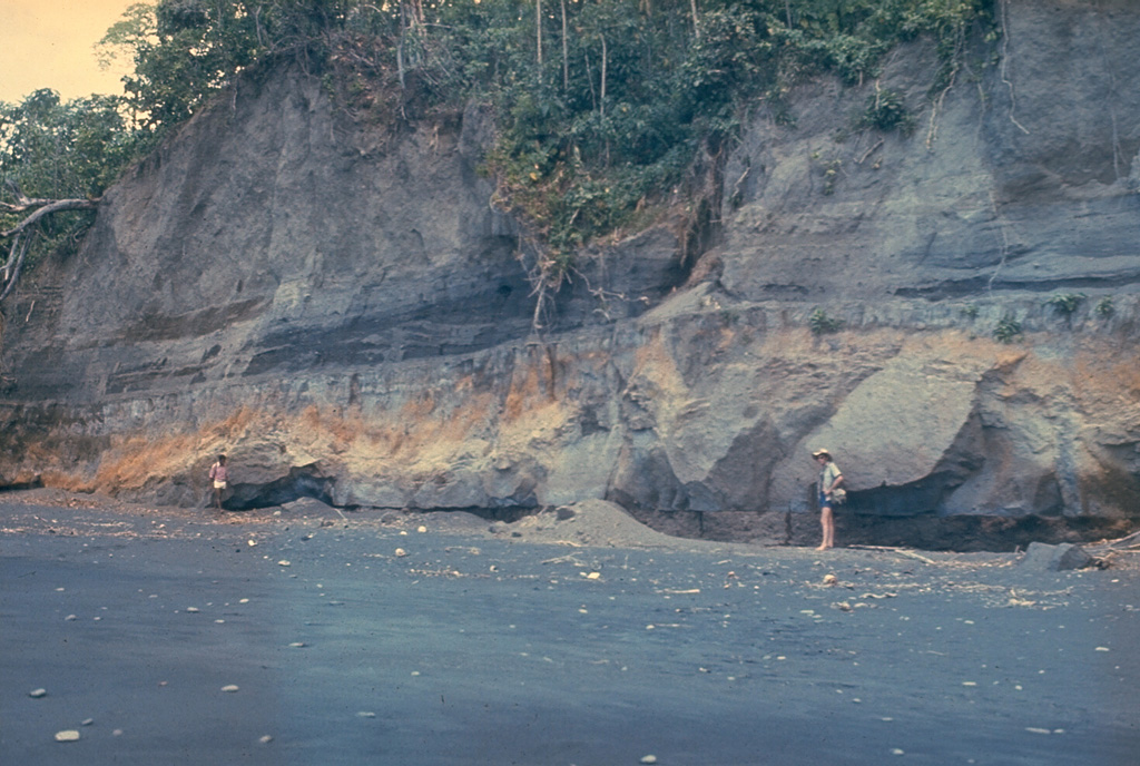 "An outcrop on the W coast of Long Island reveals deposits from the last caldera-forming eruption. This catastrophic eruption in the mid-17th century deposited ash across the New Guinea highlands and prompted legends of a ""Time of Darkness."" This outcrop shows pyroclastic surge and Plinian airfall deposits of the Matapun formation, which is exposed at the top of the section beginning about 4 m above the geologists. Photo by Russell Blong, 1975 (Macquarie University)."