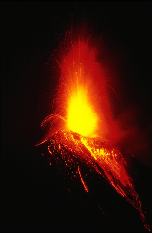 Strombolian eruptions the night of 20 November 1985 ejected incandescent bombs that fell back around the crater and tumbled down the upper flanks. Vigorous Strombolian eruptions resulted in the accumulation of large amounts of unstable material on the upper flanks that produced incandescent avalanches reaching out to 5 km from the crater. This photo was taken three days after the start of the week-long eruption. Lava flows also effused from the summit crater and traveled down the NW flank. Photo by Wally Johnson, 1985 (Australia Bureau of Mineral Resources).