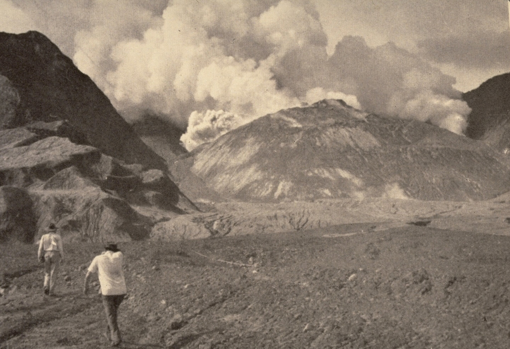 Members of a scientific team approach the crater of Mount Lamington through the avalanche valley on 11 February 1951. Explosions occurred from a vent behind the new lava dome growing in the summit crater produce gas and ash plumes. Growth of the lava dome began soon after the catastrophic 21 January explosive eruption. At the time of this photo, the smooth-surfaced lava dome was uplifting the floor of the new crater. The dome eventually grew to the height of the crater rim. Photo by Tony Taylor, 1951 (Australia Bureau of Mineral Resources).