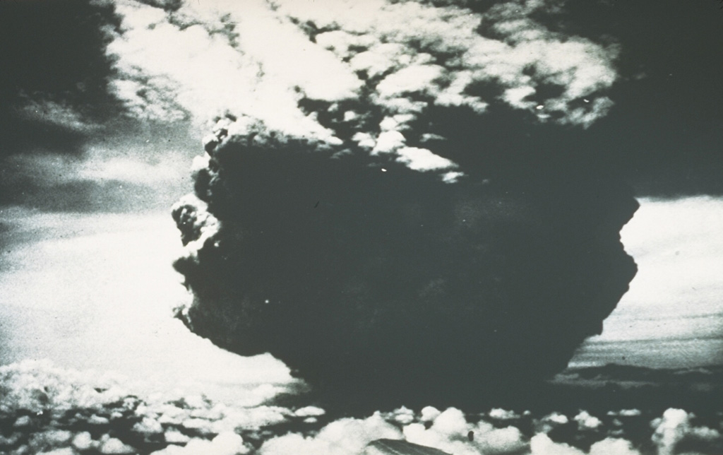 This photograph of the catastrophic eruption of 21 January 1951 was taken by the pilot flying from Port Moresby to Rabaul. From about 40 km NW, the pilot observed this ash plume rising to a height of about 13 km within two minutes. Shortly afterwards, the cloud expanded horizontally away from the volcano as devastating pyroclastic flows and surges swept radially up to 12 km from the crater. Photo by Capt. Jacobson, 1951 (published in Taylor, 1958).