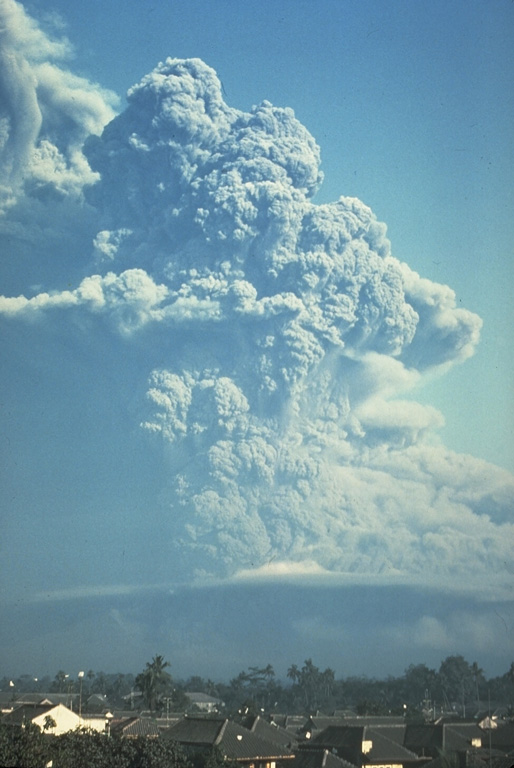 An ash plume from Galunggung volcano towers above the city of Tasikmalaya on 22 July 1982. This was one of a series of strong explosive eruptions between May and October that sometimes deposited ash and pumice on the city, located 17 km ESE of the volcano. Photo by Bob Koyanagi, 1982 (U.S. Geological Survey).