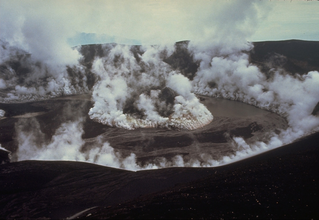 The degassing crater of Galunggung volcano on 5 February 1983, a month after the end of the 1982-83 eruption. Plumes are shown rising from a late-stage scoria cone that formed in the center of the crater and from the margins of the crater wall. A lake that had begun to form in the crater at the time of this photo eventually grew to cover the cone. Photo by Don Peterson, 1983 (U.S. Geological Survey).