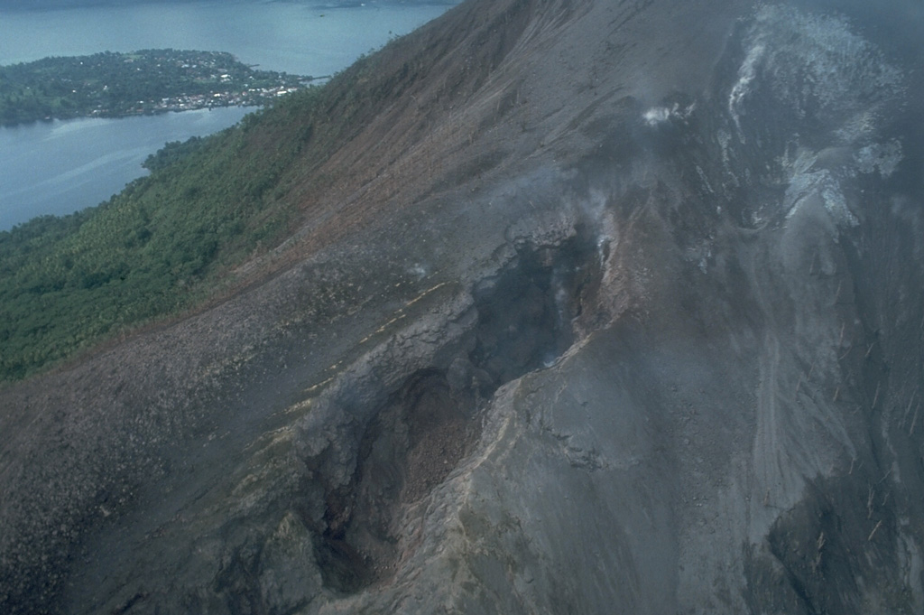 Fissures of vents no. 1 (bottom) and 3 (upper right) cut the northern flank of Banda Api volcano.  Ash mantles vegetation adjacent to the fissures, which are about 15-20 m wide at this location.  These vents, which began erupting on May 9, 1988, also fed two large lava flows that reached the sea along the northern and NW coasts.  Neira Island appears in the background in this May 21, 1988 photo. Photo by Tom Casadevall, 1988 (U.S. Geological Survey).