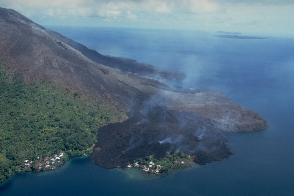 This May 19, 1988, view from the NE shows a still-steaming black lava flow entering the sea along the north coast, partially overrunning the village of Batu Angus.  The lava flow originated from a vent at 200 m on the north flank on May 9, and reached the sea the same day.  A second steaming lava flow, the Pasir Besar flow, which originated from a vent at 300-350 m elevation, can be seen reaching the NW coast at the center of the photo.  The portion of Batu Angus village surrounded by the lava flow sits on an earlier lava flow erupted in 1901. Photo by Tom Casadevall, 1988 (U.S. Geological Survey).