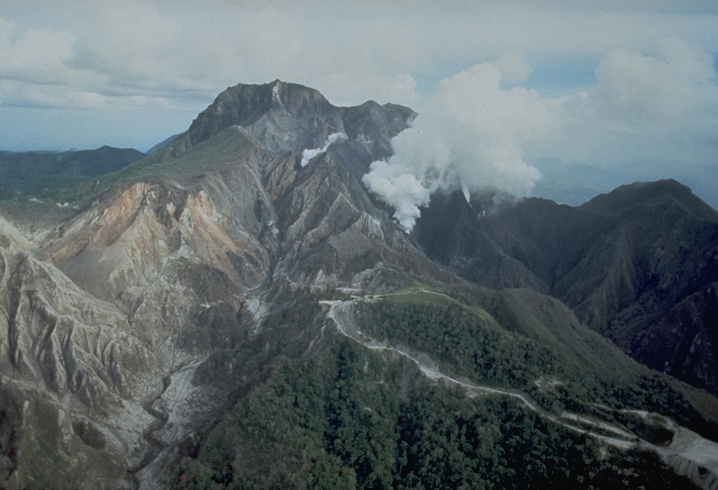An aerial view of the north flank of Pinatubo shows the area devastated by explosions on 2 April 1991. This eruption was the first in a progressively intensifying series of eruptions that led to collapse of the summit and caldera formation on 15 June. The road in the foreground provided access to a geothermal drill station. Photo by Chris Newhall, 1991 (U.S. Geological Survey).