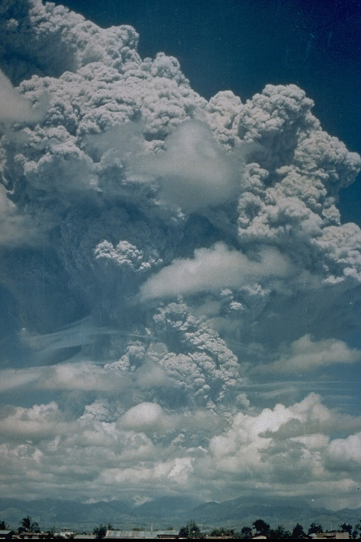 A large Plinian ash plume towers above Pinatubo in the Philippines on 12 June 1991, reaching an altitude of 19 km. This was the first in a series of powerful eruptions that culminated on 15 June with a series of major pyroclastic flows that traveled down all sides of the volcano. Collapse of the summit then created a 2.5-km-wide caldera. This photo was taken from Clark Air Base, about 25 km ENE of Pinatubo. Photo by Karin Jackson, 1991 (U.S. Air Force).