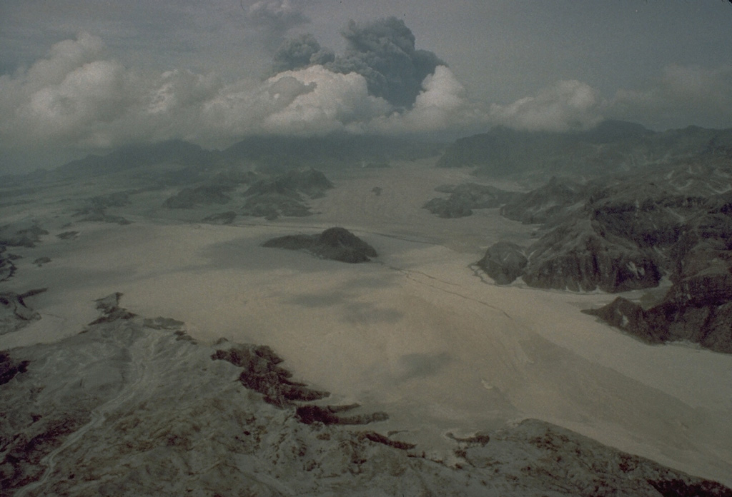 Voluminous pyroclastic flows on 15 June 1991 descended all sides of Mount Pinatubo in the Philippines. The flat, light-colored areas in the foreground are pyroclastic flow deposits that filled the Marella River valley on Pinatubo's SW flank to a depth of 200 m. The dark hill at the center was completely surrounded by pyroclastic flows that traveled 14 km down this valley. Photo by Rick Hoblitt, 1991 (U.S. Geological Survey).