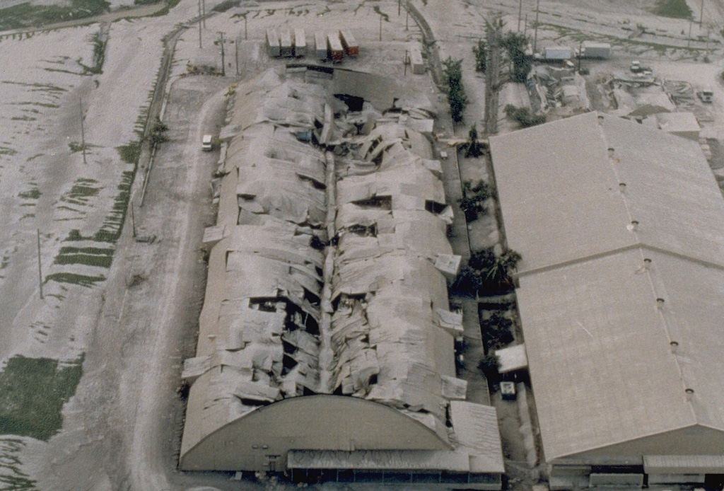 Heavy ashfall from the 15 June 1991 eruption of Pinatubo volcano caused the roof of this warehouse at Clark Air Base. The base had been evacuated prior to the eruption climax on the 15th. Photo by R. Batalon, 1991 (U.S. Air Force).