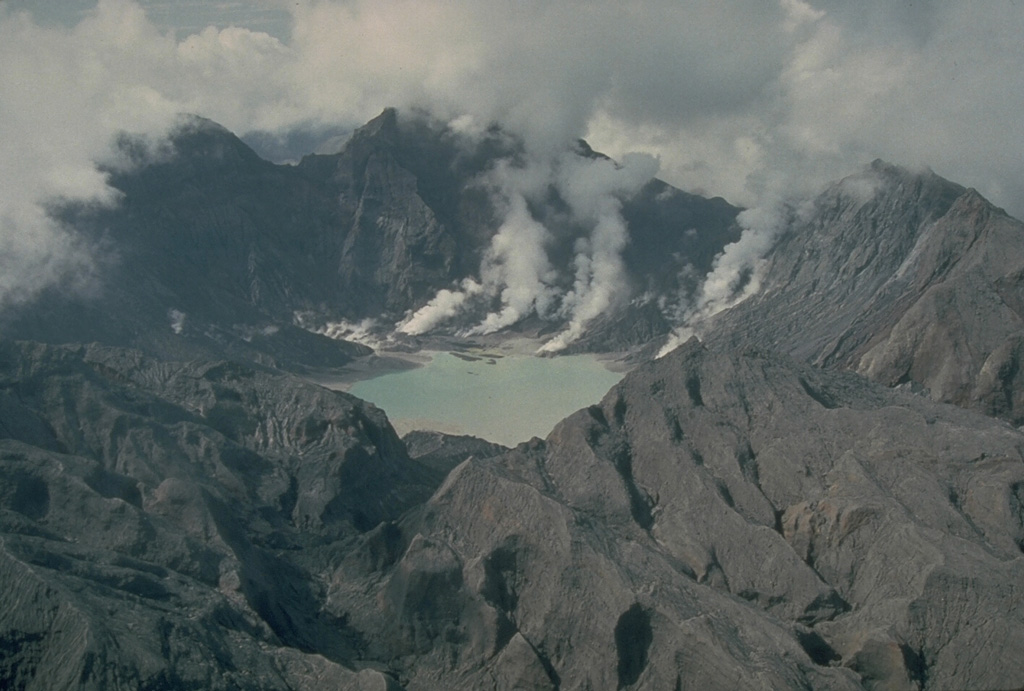 The major explosive eruption on 15 June 1991 created a 2.5-km-wide caldera at the summit of Pinatubo. The elevation of the caldera floor is more than 900 m below that of the pre-eruption summit. Plumes rise from fumaroles on the caldera floor in this 4 October 1991 photo taken from the N. The outer flanks of the caldera are stripped of vegetation and covered with ash and pyroclastic surge deposits. Photo by Chris Newhall, 1991 (U.S. Geological Survey).
