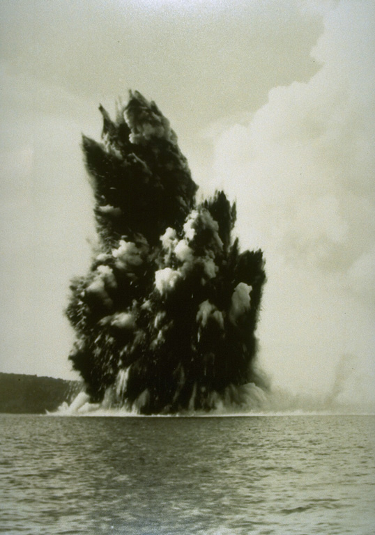 Submarine eruptions within Krakatau caldera were first observed in December 1927 and an ephemeral island appeared the following month. This 1929 view shows an ash-rich cock's tail jet typical of shallow submarine explosions. Material ejected by earlier eruptions forms an island visible to the left. By August 1930 Anak Krakatau became a permanent island. Photo by C.E. Stehn, 1929 (courtesy Volcanological Survey of Indonesia).