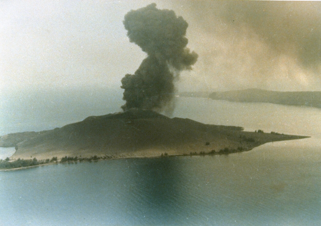 An explosive eruption in 1979 from Anak Krakatau is seen in an aerial view from the north. The island of Anak Krakatau, a post-caldera cone that has grown within the submarine caldera of 1883, first breached the surface in 1928. Photo by Adjat Sudradjat, 1979 (Volcanological Survey of Indonesia).