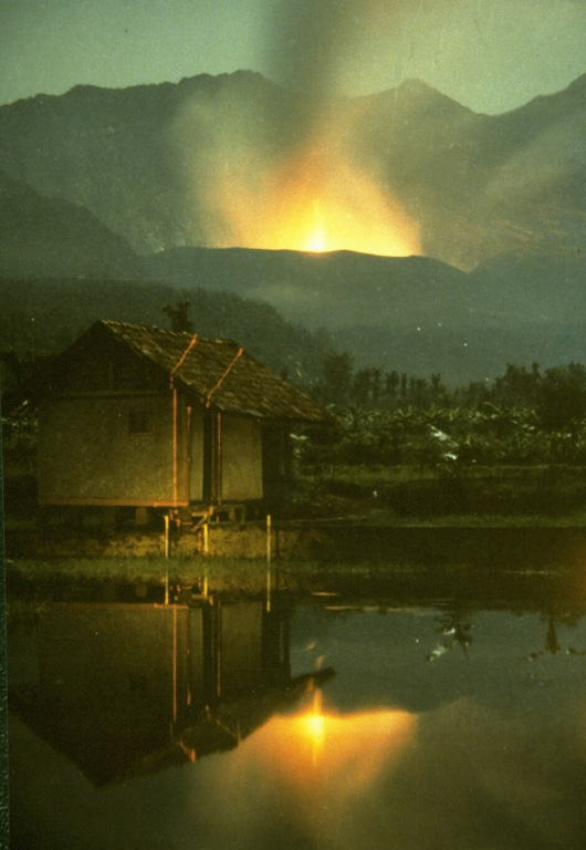 Strombolian eruptions from the crater of Galunggung volcano on 23 December 1982 are reflected in a pond at Kubanghurang village, SE of the volcano. The vertical orange lines crossing the house at the left are the traces of an Electronic Distance Measurement (EDM) laser used by Volcanological Survey of Indonesia scientists to monitor deformation of the volcano. Photo by Ruska Hadian, 1982 (Volcanological Survey of Indonesia).