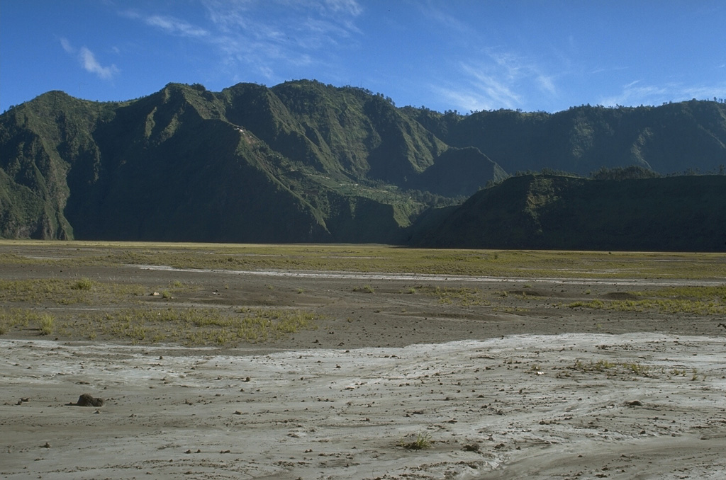 Two caldera walls can be seen in this view across the flat Sandsea caldera floor. The low ridge in the shadow in the foreground is the northern wall of the younger Tengger (Sandsea) caldera, which merges at the upper left with the background ridge, the northern wall of the 16-km-wide Ngadisari caldera. Photo by Lee Siebert, 1995 (Smithsonian Institution).