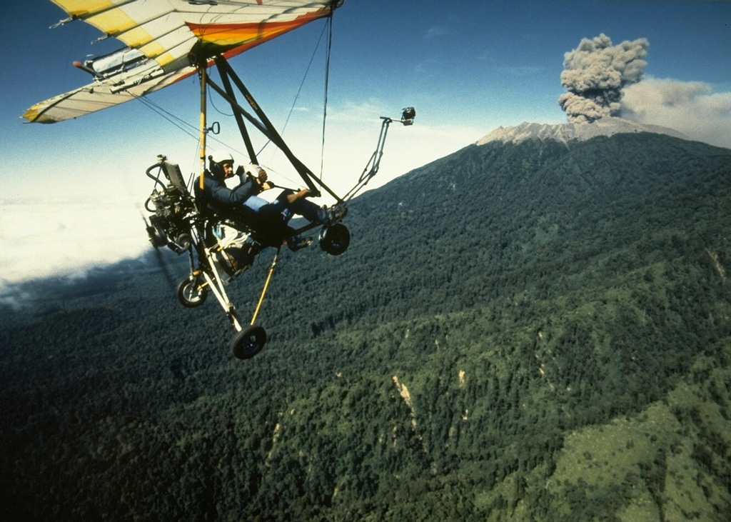 An ultralight aircraft was used by scientists from France and the Volcanological Survey of Indonesia to monitor activity at Raung in 1988. This July view shows an ash plume rising above the forested northern flank of Raung volcano. Hundreds of explosive eruptions were recorded during August and September 1988. This eruption began in 1987 and continued into 1989. Photo by Willem Rohi, 1988 (Volcanological Survey of Indonesia).