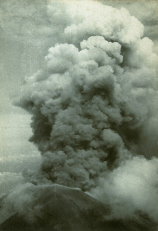 An ash plume rises above the summit crater of Agung volcano on 17 March 1963 during the first of two powerful explosive eruptions that caused much devastation to the island of Bali. The eruption began on 19 February with a lava flow that traveled down the N flank. Major explosive events occurred on 17 March and 16 May that produced devastating pyroclastic flows and lahars that killed more than 1,100 people. Photo by Djazuli, 1963 (Volcanological Survey of Indonesia).