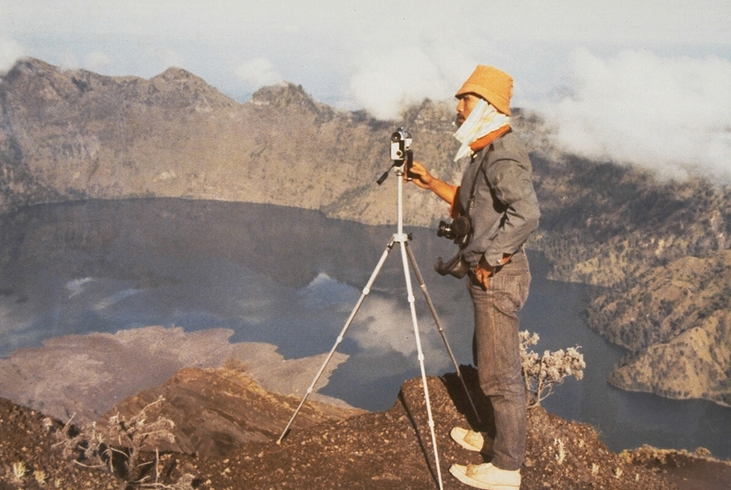 A scientist from the Volcanological Survey of Indonesia makes theodolite measurements along the N rim of the 5-km-wide Segara Anak caldera of Rinjani on Lombok Island. The lobate lava flow entering the lake at the lower left was erupted in 1944 from a vent on the NW flank of Gunung Barujari. Photo by Sumarna Hamidi, 1973 (Volcanological Survey of Indonesia).