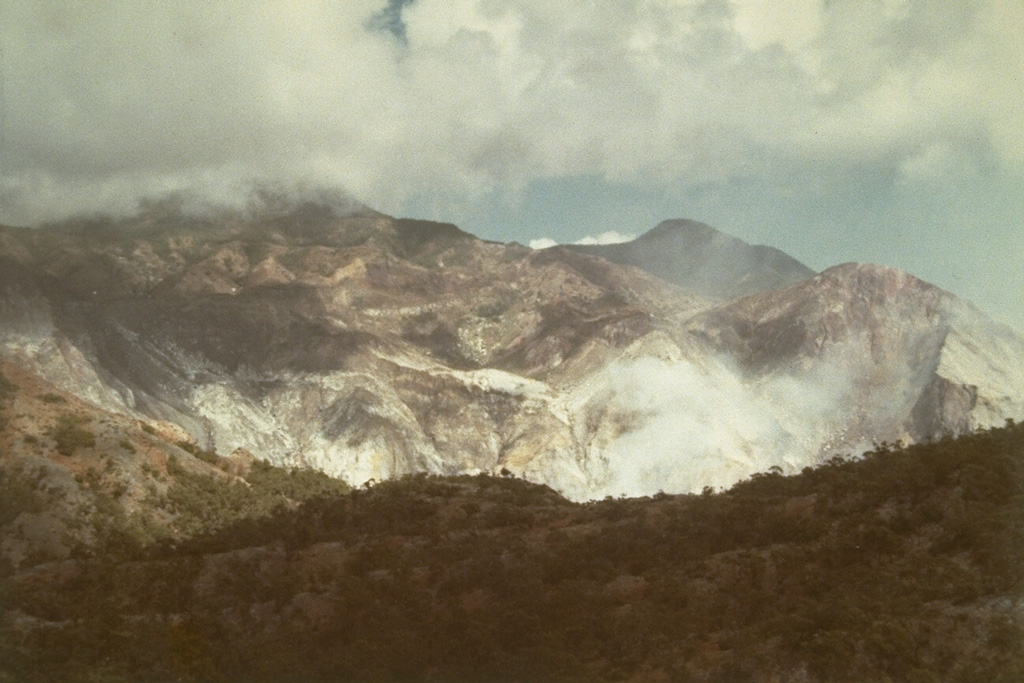 Steam clouds rise above a fumarole field on the flank of Gunung Sirung, south of Airmama village.  The crater walls contain extensive areas of light-colored hydrothermally altered rock.  Photo by L.D. Reksowirogo, 1972 (Volcanological Survey of Indonesia).