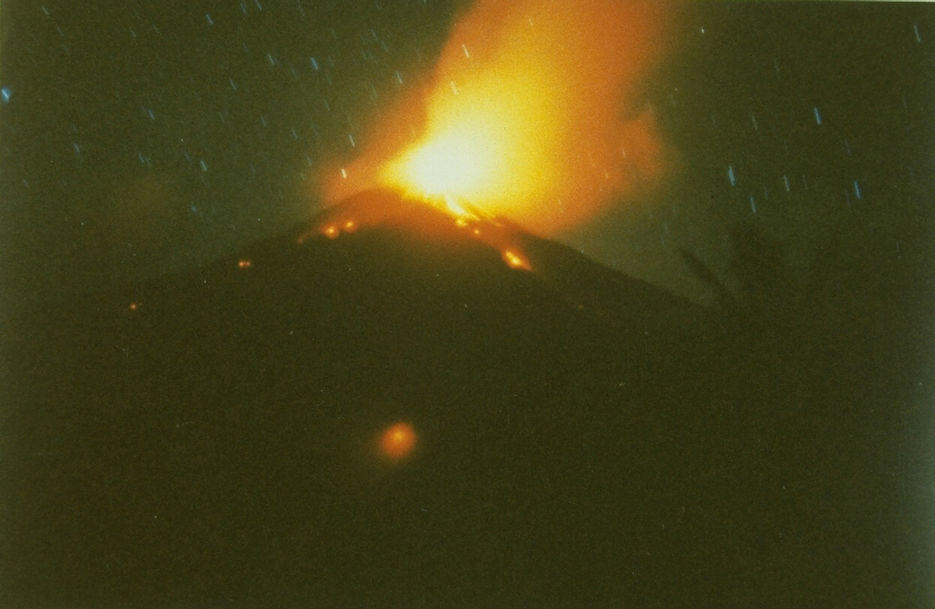 A time exposure captures a nighttime view from the south of explosive eruptions at the summit of Karangetang volcano in February 1985, part of an eruption that began in May 1983 and lasted until the end of 1988.  On February 24, 1985, a new vent opened on the south flank, sending a lava flow down the Batuawang River. Photo by S.R. Wittiri, 1985 (Volcanological Survey of Indonesia).