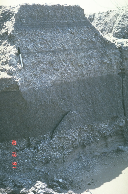 These relatively fine-grained layers are lahar deposits produced by successive overflows of dikes along the Bambam River, about 35 km NE of Pinatubo volcano in the Philippines. The photo was taken on 13 October 1991, a little more than a month after the end of the devastating 1991 eruption. Note the pen at the upper left for scale. By the end of 1991, rainfall-induced lahars had traveled 50 km down the Bambam River. Photo by Chris Newhall, 1991 (U.S. Geological Survey).