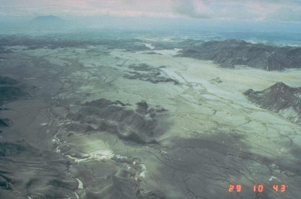 The broad, light-colored areas are thick deposits of pyroclastic flows from the 15 June 1991 eruption of Pinatubo. This 29 June photo taken two weeks after the eruption is looking towards the east with Clark Air Base just beyond the margin of the pyroclastic flow fan. Erosion of the unconsolidated pumice and ash since 1991 has extensively dissected the fan. Mount Arayat is visible at the upper left. Photo by Ed Wolfe, 1991 (U.S. Geological Survey).