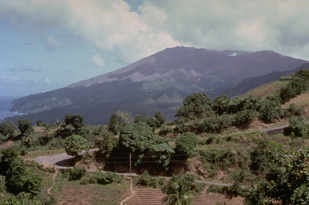 Soufrière volcano, seen here from the south, forms the northern end of the island of St. Vincent.  Its broad, flat summit is formed by several generations of craters.  The present-day, 1.6-km-wide crater, cut on its NE side by a smaller crater formed in 1812, has been the site of lava dome formation and explosive removal on several occasions since the first historical eruption in 1718.  Pyroclastic flows from eruptions in 1812, 1902, and 1979 reached the coast. Photo by Richard Fiske, 1980 (Smithsonian Institution).