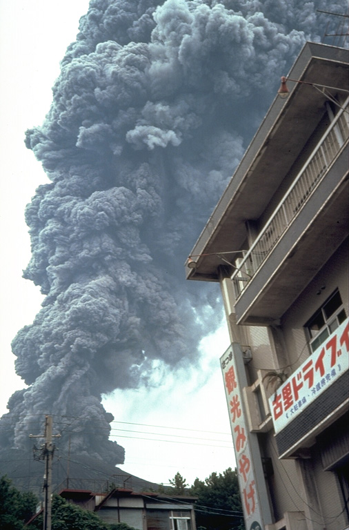 An ash plume rises above a restaurant on Sakurajima island in September 1981. Near-continuous explosive eruptions have been occurring since 1955. Residents on the island coexist with the volcano, which frequently deposits ash on residential areas. Occasional larger explosions have ejected ballastic blocks that have penetrated concrete roofs of buildings. Villages on Sakurajima are located along the island's coast, but most are only 3-5 km from Minamidake, the active summit crater. Copyrighted photo by Dick Stoiber, 1981 (Dartmouth College).