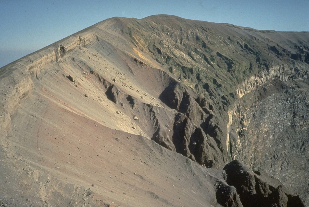 The upper crater rim of Vesuvius is capped by thick tephra deposits from the last eruption episode in 1944. The bedded tephra layers overlie a light-colored layer at the right, a lava flow that had been erupted earlier in the 1944 eruption. The steep wall beneath the 1944 lava flow cuts through pre-1944 lava flows. Photo by Roberto Scandone, 1989 (University of Rome).