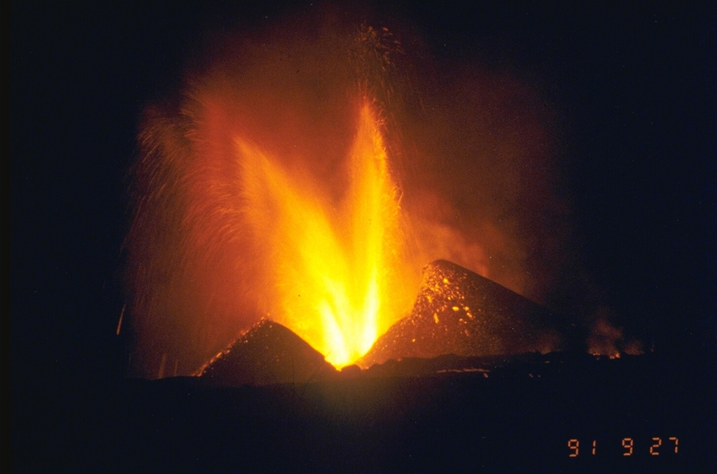 An eruption began on 20 September 1991 on the NE flank, 15 km from the summit. This was the northernmost historical eruption site of Nyamuragira. Lava fountaining from the new Mikombe cone is seen here on 26 September (the 27 September date-time stamp is in Japan Standard Time). Lava flows extended 6-7 km to the NE, cutting the road to Tongo. The eruption became more explosive on 20 November, and by July 1992 had built 26 scoria cones along a NE-trending fissure zone. The eruption continued until 8 February 1993. Photo by Minoru Kasahara, 1991 (Hokkaido University).