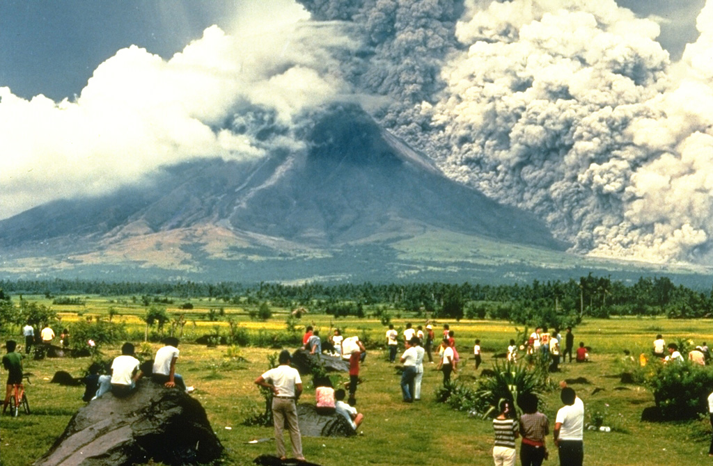 A crowd of spectators watches a pyroclastic flow sweeping down the SE flank of Mayon volcano on 24 September 1984. They stand on the surface of a deposit from a large lahar emplaced during an eruption in 1814. The pyroclastic flow seen here traveled about 6 km. Strong explosions the previous day created notches in the SE and east crater rims that funneled pyroclastic flows down ravines in those directions. Photo by Norm Banks, 1984 (U.S. Geological Survey).