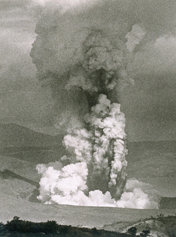 An ash plume rises above a vent on the SW side of Volcano Island on 30 September 1965. The white plume at the base is a horizontally moving base surge. Devastating pyroclastic surges were produced during the two-day eruption, which began on 28 September and caused 150 fatalities. Photo by L.E. Andrews, 1965 (courtesy of Jim Moore, U.S. Geological Survey).