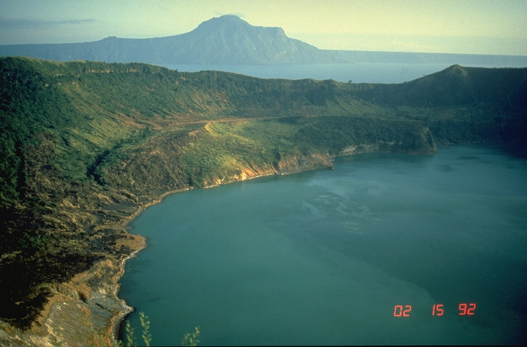 This view of Main Crater Lake, filling a small 3-km-wide caldera on Volcano Island, looks across distant Lake Taal to the NE rim of the 15 x 20 km Taal caldera. The surface of the 267 km2 lake is only 3 m above sea level. Volcano Island has been the source of all historical eruptions. Explosive eruptions have produced pyroclastic surges that swept across Lake Taal and devastated lakeshore areas. Pleistocene eruptions that formed the caldera greatly modified the topography of southern Luzon Island. Photo by Chris Newhall, 1989 (U.S. Geological Survey).
