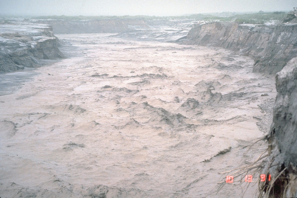 A lahar, or volcanic mudflow, fills the banks of the Pasig-Potrero River on the east side of Pinatubo volcano in the Philippines on 13 October 1991. The lahar moved at a velocity of 3-5 m/s and carried a few meter-sized boulders. This lahar was not directly produced by an eruption, but was triggered by minor rainfall that remobilized thick deposits of ash and pumice that blanketed the landscape. Devastating lahars occurred at Pinatubo for years after the catastrophic 1991 eruption. Photo by Chris Newhall, 1991 (U.S. Geological Survey).