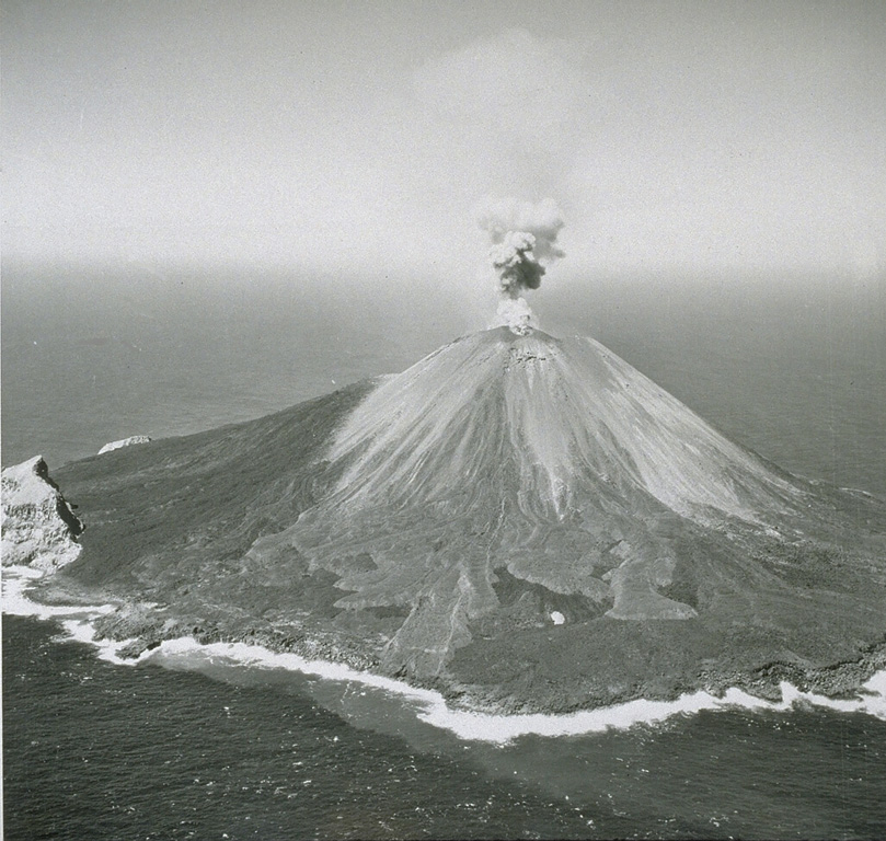 Explosive activity was frequently observed from Farallon de Pajoras volcano in October and November 1952. Lava flows were emplaced on the E and W sides of the summit in February-March 1953. This 1953 photo from the E shows a small plume rising above the summit crater and lighter-gray lava flows in the center that erupted in 1953. The lobe just left of center eventually reached the coast. Explosive activity continued until 15 April. The steep-sided peak on the SE coastline is a remnant of an older caldera. Photo by U.S. Navy, 1953.