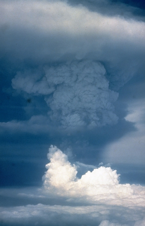 An ash plume towers above Pagan volcano on 18 May 1981, three days after the onset of the eruption. The initial eruption on 15 May produced ash plumes that rose to estimated heights of 16-20 km. Three vents along a fissure formed across the summit on 15 May. An upper NE flank cone produced a new scoria cone, and vents on the N and S summit crater rims produced lava flows that traveled down the flanks. Intermittent explosive activity continued until 1985. Photo by Gary Haust, 1981 (courtesy Norm Banks, U.S. Geological Survey).