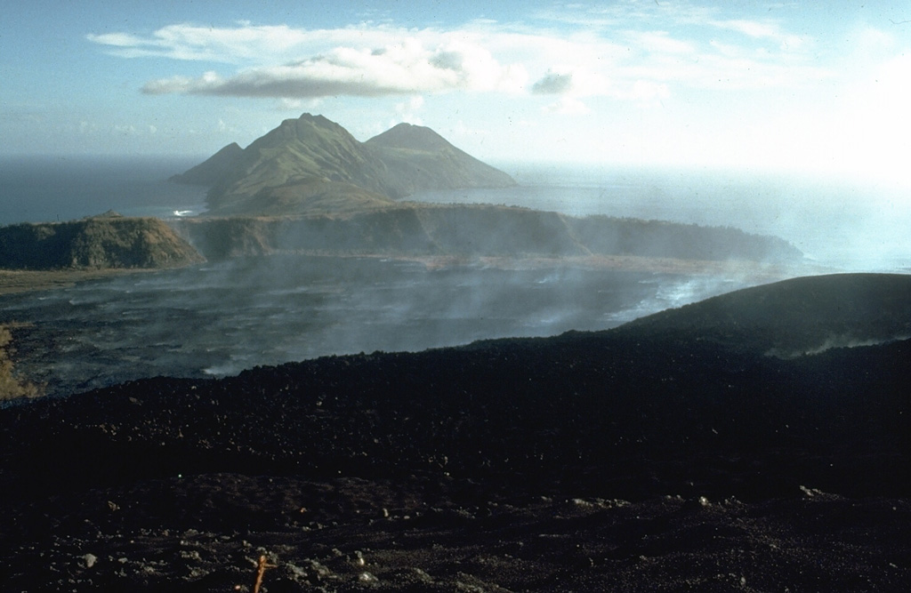 Gases rise from a lava flow that is advancing below the S flank of Pagan in 1981. The flow erupted during 15-26 May 1981 from a vent on the S crater rim and spread out over the broad caldera floor, eventually reaching the southern caldera wall. The foreground area on the flanks of Pagan consists of pyroclastic surge deposits from the 1981 eruption. This 21 May 1981 photo looks to the SW with South Pagan volcano forming the conical peak at the right. Photo by Norm Banks, 1981 (U.S. Geological Survey).