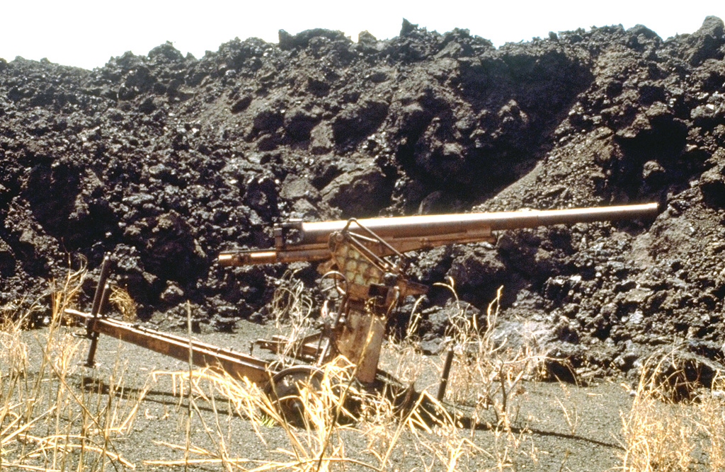 The SW-flank lava flow from the May 1981 eruption overran a Japanese World War II bunker and ashfall from the eruption partially buried this anti-aircraft gun. The lava flow traveled 3 km from its vent on the south crater rim. Other flows traveled down the north flank almost to the coast. Photo by Norm Banks, 1981 (U.S. Geological Survey).