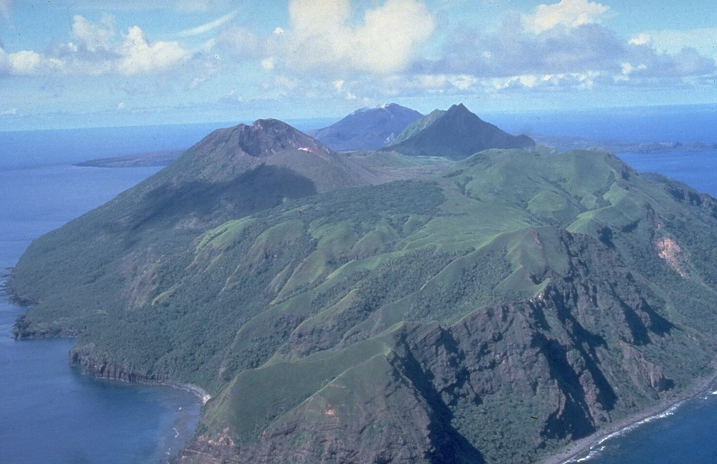 South Pagan volcano occupies the SW end of Pagan Island and has four craters. The ridge in the right foreground is the eroded rim of a 4-km-wide caldera containing the volcano. Eruptions volcano occurred during the 19th century, but it has been much less active than North Pagan, the peak at the far center on the NE tip of the island. Photo by U.S. Navy, 1981.