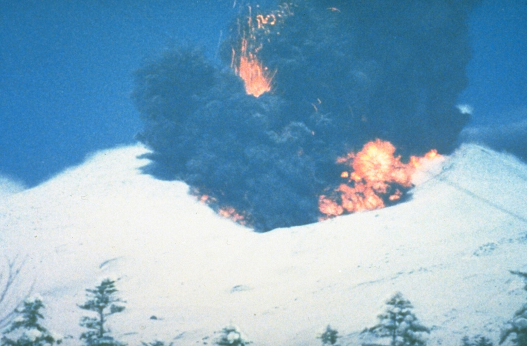 A phreatomagmatic explosion on 25 December 1988 at Japan's Tokachi volcano ejects incandescent blocks and a dark ash cloud. At the base of the ash plume is the leading edge of a small pyroclastic surge that eventually traveled down the N flank to 1 km from the vent. The 1988 eruption began with a phreatic explosion on 16 December. Intermittent explosive eruptions with small pyroclastic flows and surges began on 19 December and continued until 5 March 1989. Photo courtesy of Japan Meteorological Agency, 1988.
