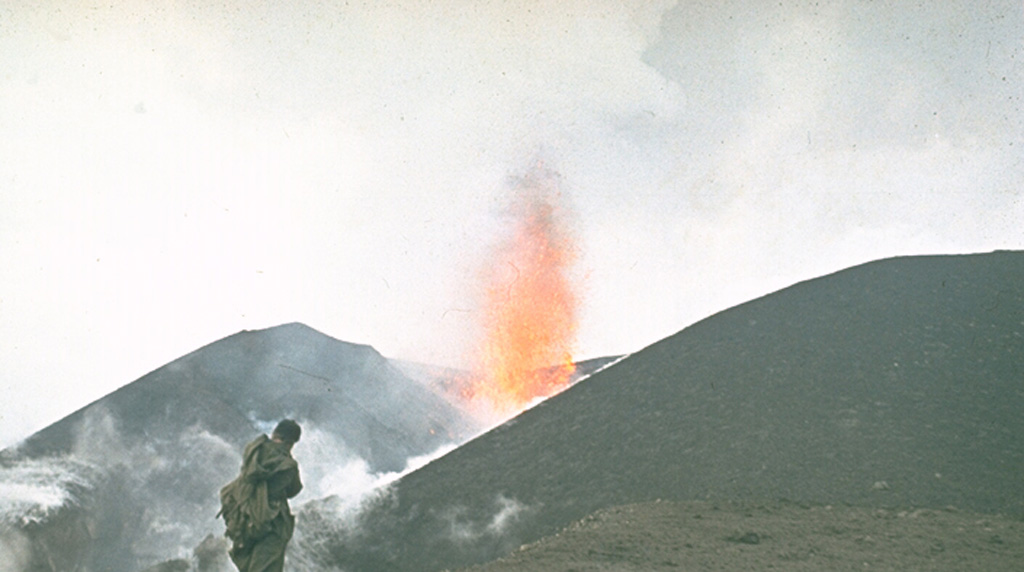 A volcanologist from the Institute of Volcanology in Petropavlovsk observes a lava fountain from an Alaid scoria cone in 1972. The eruption began on 18 June and lasted until 11 September. A chain of small cones was formed on a 2-km-long fissure on the lower NW flank and lava flows reached the sea and formed a new peninsula. Photo by Yuri Doubik, 1972 (Institute of Volcanology, Petropavlovsk).