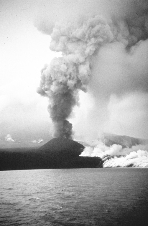The 1972 eruption of Alaid volcano in the northern Kuril Islands, seen here in August, was characterized by both explosive and effusive activity. An ash plume towers above a small scoria cone that formed on a 2-km-long fissure on the NW flank, while white gas-and-steam plumes rise from the margins of a lava flow that traveled 1 km into the Sea of Okhotsk. The eruption began on 18 June and ended by 11 September. Photo by A.M. Chirkov, 1972 (courtesy of Oleg Volynets, Institute of Volcanology, Petropavlovsk).
