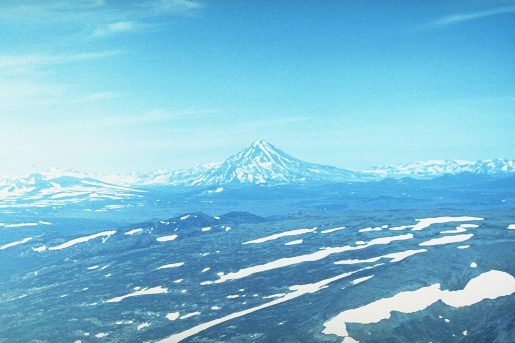 Mutnovsky (center) one of the most active volcanoes of southern Kamchatka and is formed of four coalescing edifices, seen here from the west. The complex has multiple summit craters and historical eruptions have been explosive, with lava flows produced during 1904.  Photo by Andrei Tsvetkov.