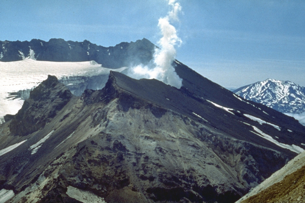 The glacier-filled southern summit crater of Mutnovsky is seen here from the NE with Asacha in the distance. This crater is within a larger 1.5 x 2.1 km wide crater with walls 50-250 m high. Four smaller craters are on the northern rims of the summit crater complex. A steam plume rises from the historically active crater on the western rim of northern Mutnovsky crater. Photo by Oleg Volynets (Institute of Volcanology, Petropavlovsk).