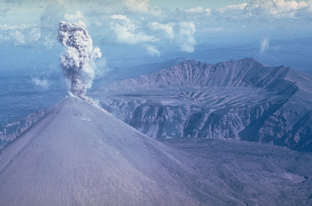 This ash plume rising above the summit of Karymsky during the early 1970's represents typical activity during its 1970-1982 eruption. It was constructed within a 5-km-wide caldera that formed about 6,000 years ago. The northern Karymsky caldera wall is seen across the center of the photo. It formed within the older Dvor caldera, with the caldera wall visible in the background. Photo by Yuri Doubik, 1972 (Institute of Volcanology, Petropavlovsk).
