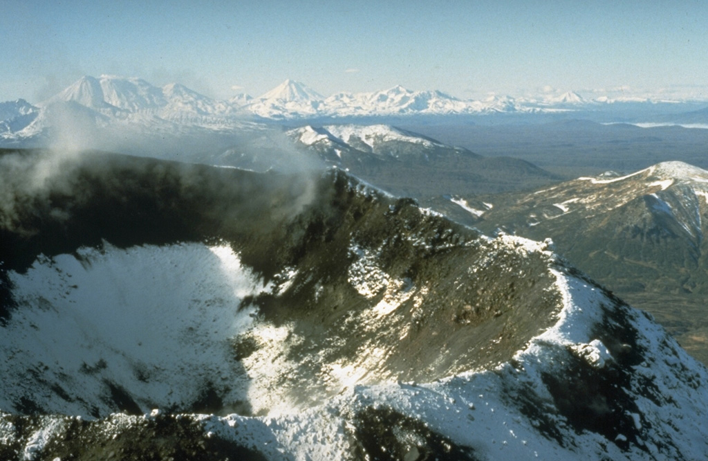 The 200-250 m wide Karymsky summit crater formed following a long-term eruption during 1970-82. This early 1990's photo shows the crater from the NE. Several other prominent central Kamchatka volcanoes are in the background. Zhupanovsky, to the far left, is composed of four overlapping edifices constructed along an WNW-ESE line. Koryaksky is to the left-center, and the broad Dzenzursky massif to its right. Photo by Dan Miller (U.S. Geological Survey).
