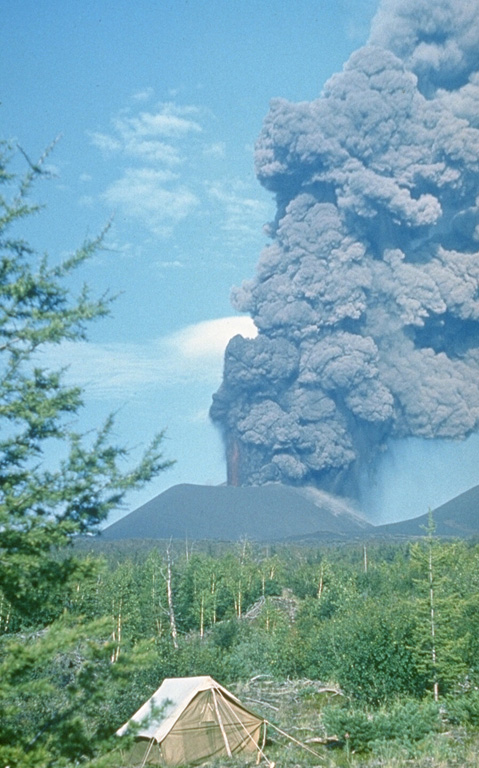 An ash plume rises above a scoria cone along the S-flank rift zone of Kamchatka's Tolbachik volcano in late July 1975. This was the first of three cones formed along the northern part of the rift zone during the early stage of the eruption and was only a few weeks old at the time of this photo. Lava fountains rose 1-2.5 km above the vent and ash plumes reached 10-18 km heights. Photo by Oleg Volynets, 1975 (Institute of Volcanology, Petropavlovsk).