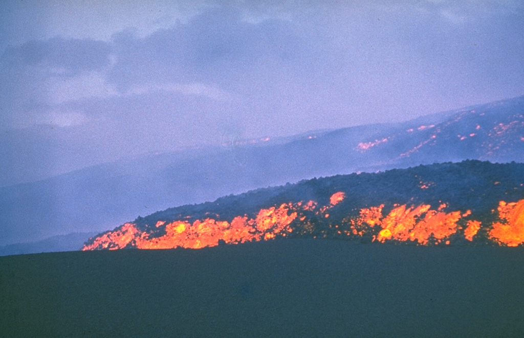 "The incandescent lava flow front advances across an ash-covered surface in July 1975. Incandescence can also be seen in the main body of the flow behind it. This lava flow, the first of the ""Great Tolbachik Fissure Eruption"" of 1975-76, originated from the first of three large scoria cones that formed at the northern of two principal eruption sites. Photo by Anatolii Khrenov, 1975 (courtesy of Oleg Volynets, Institute of Volcanology, Petropavlovsk)."