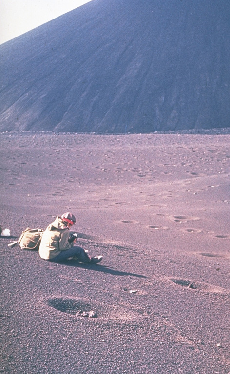 A scientist from the Institute of Volcanology studies tephra produced during the 1975-76 eruption of Kamchatka's Tolbachik volcano. The circular pits were formed by the impact of dense volcanic blocks and bombs. The blocks, one of which can be seen in the closest pit, originated from the scoria cone in the background. Photo by Oleg Volynets, 1975 (Institute of Volcanology, Petropavlovsk).
